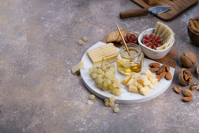 Cheese board with delicous cheeses, walnuts, honey and grapes, copy space
