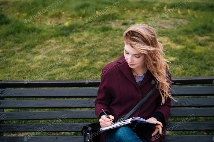 Thoughtful woman sitting on bench and writing in notebook outdoors