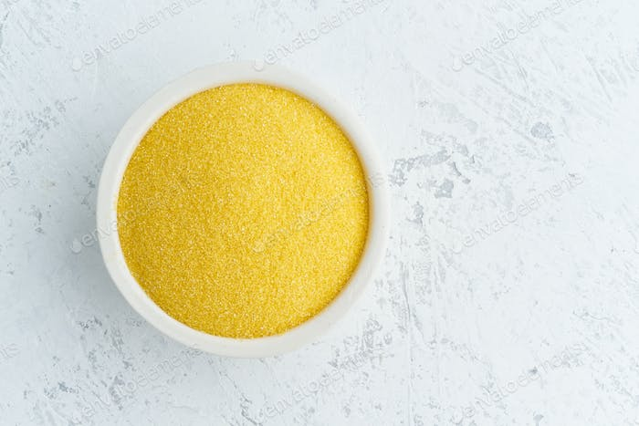 Corn, polenta in white bowl on white background. Dried cereals in cup, vegan food