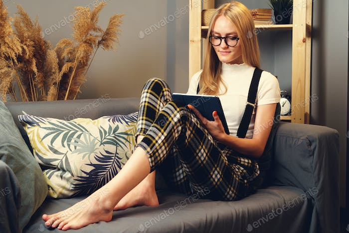 Woman at night home surfing on internet with digital tablet. Stay at Home