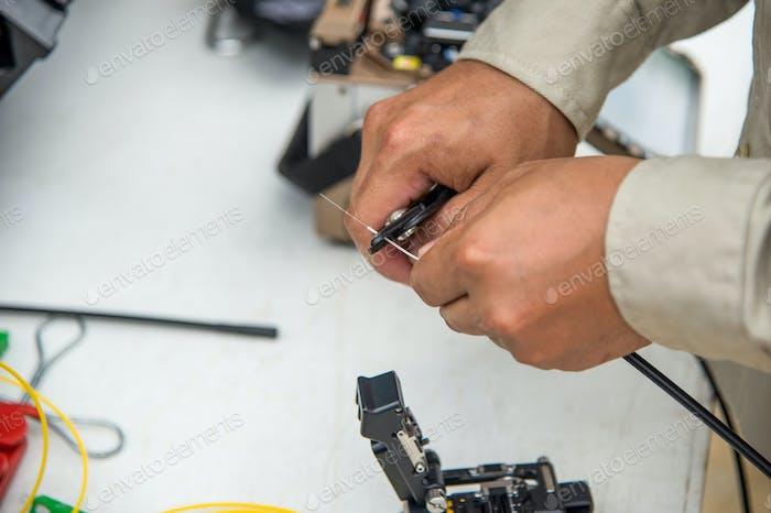 Technicians are cutting fiber optic cables.