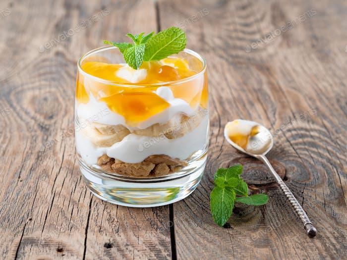 Gesundes mehrschichtiges Dessert mit Joghurt, Banane, Mango-Marmelade, Cookie auf Holzhintergrund, Seitenansicht