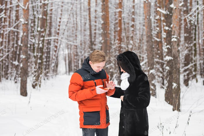 Happy couple consulting a smart phone in winter outdoors