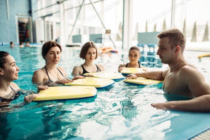 Trainer swims with class on aqua aerobics workout