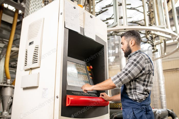 Young worker choosing settings of processing on display