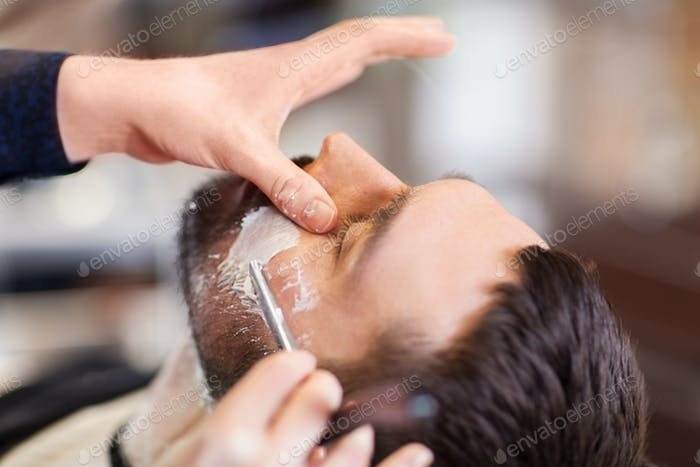 man and barber with straight razor shaving beard
