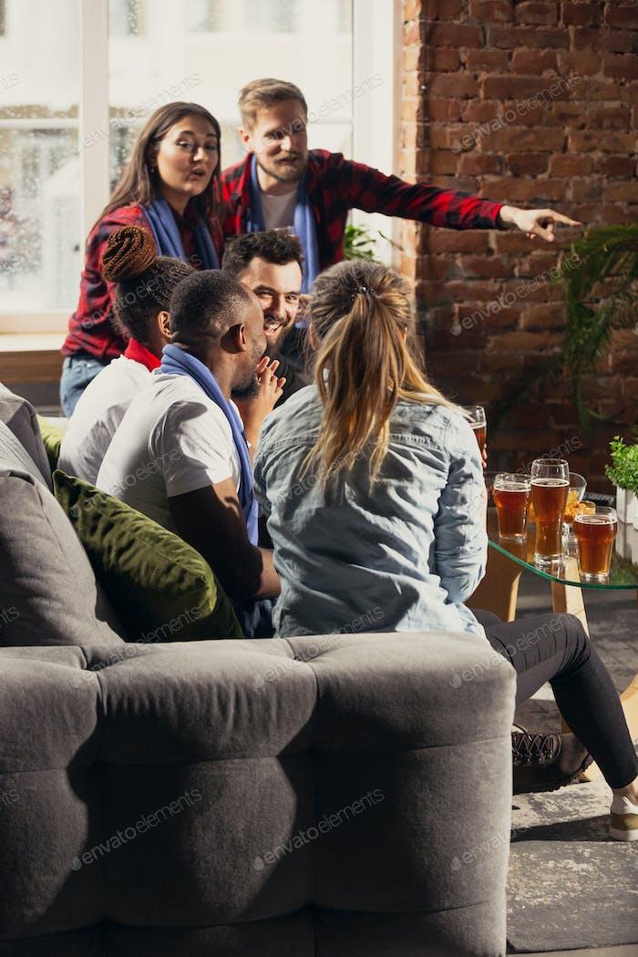 Возбужденную группу людей, которые смотрят футбол, спортивный матч дома