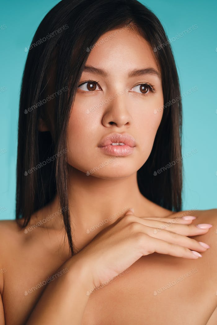 Portrait of gorgeous Asian brunette girl thoughtfully looking away over colorful background