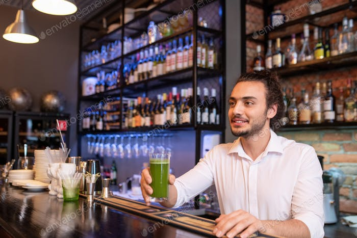 Young smiling barman holding glass of green salary cocktail or smoothie