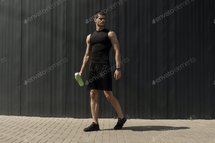 Athletic modern young man posing on a gray metallic wall copy space