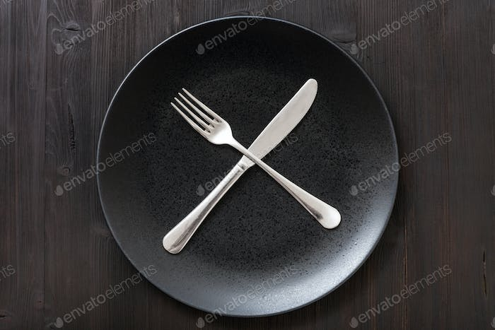top view black plate with flatware on dark brown