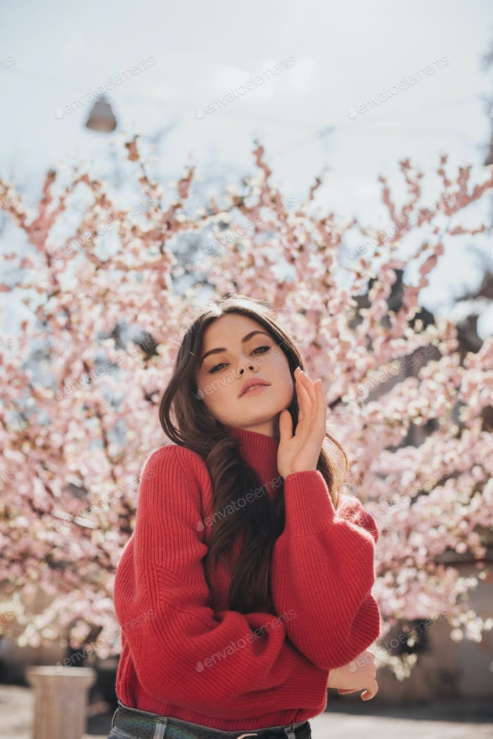 Attractive woman in bright sweater looks into camera on background of sakura. Snapshot of lady in r