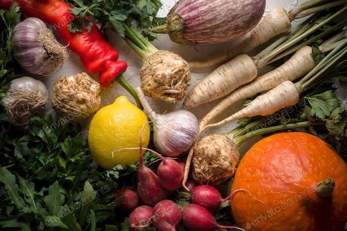 Background of celery roots, parsley, radishes with leaves and garlic, pumpkins and chili