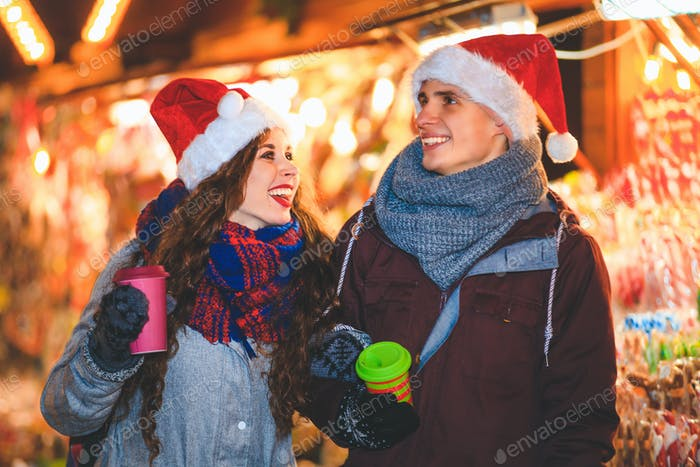 Happy couple in warm clothes with hot drinks enjoying Christmas market at evening