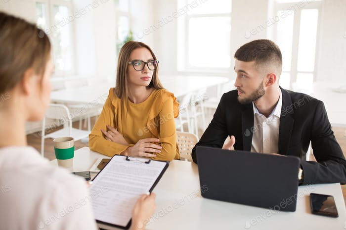 Young business man with laptop and business woman in eyeglasses