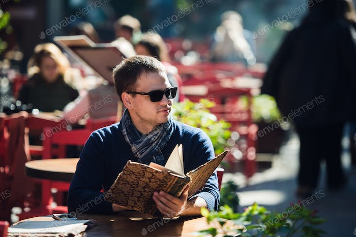 Young handsome man wearing sunglasses reading the morning paper in a street cafe looking sideways