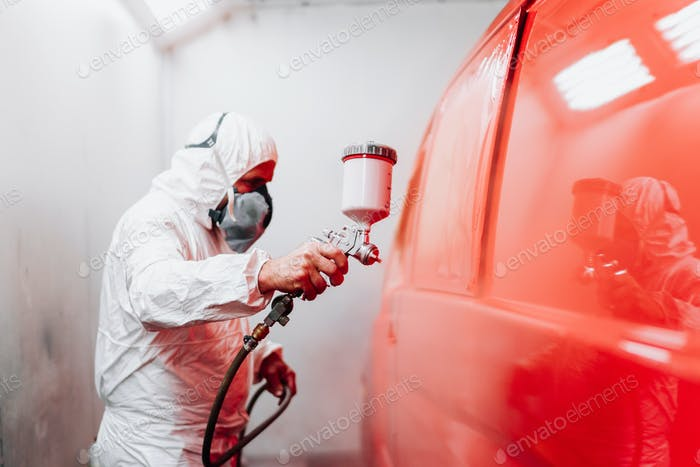 Auto manufacturing industry worker with spray gun with red paint painting a car in special booth