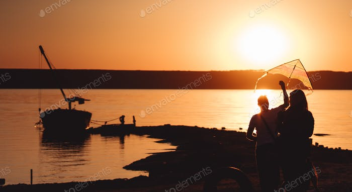 A young couple on the shore launches a kite