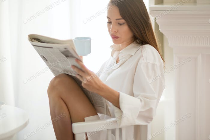 Beautiful woman reading morning paper