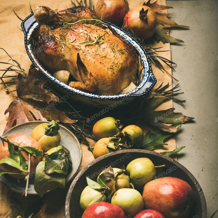 Thanksgiving dinner table with roasted meat, vegetables, fruit, square crop