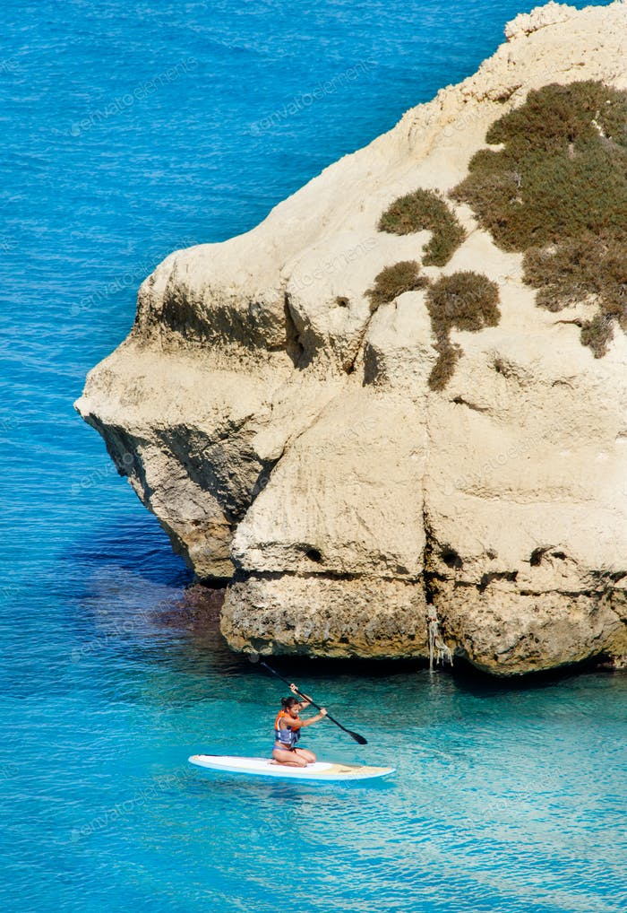 Girl on a sup in the shore of Torre dell'Orso