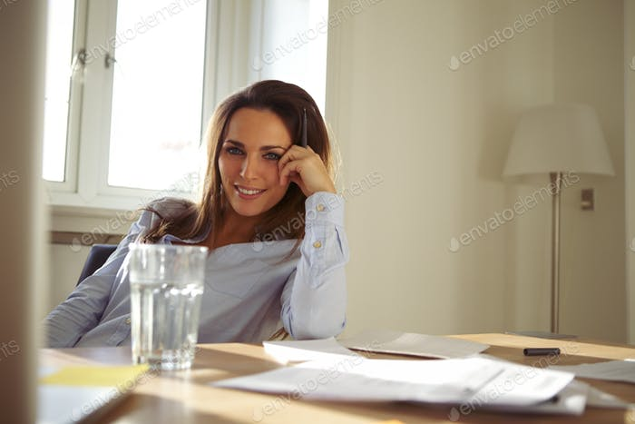 Pretty caucasian businesswoman at home office desk