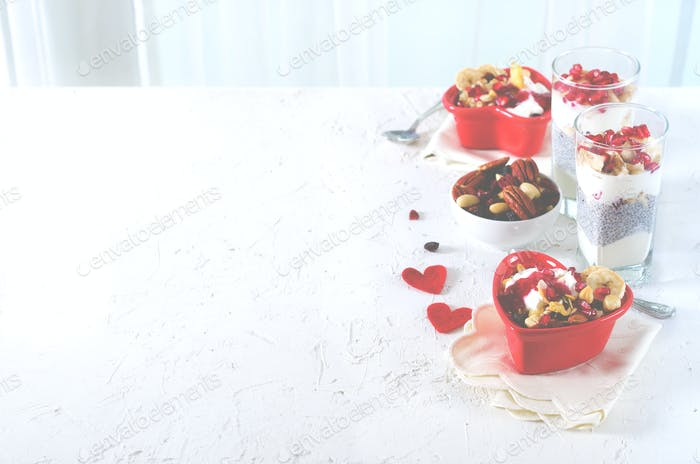 Healthy breakfast - pomegranate, yogurt, granola parfait on white concrete background. Romantic time