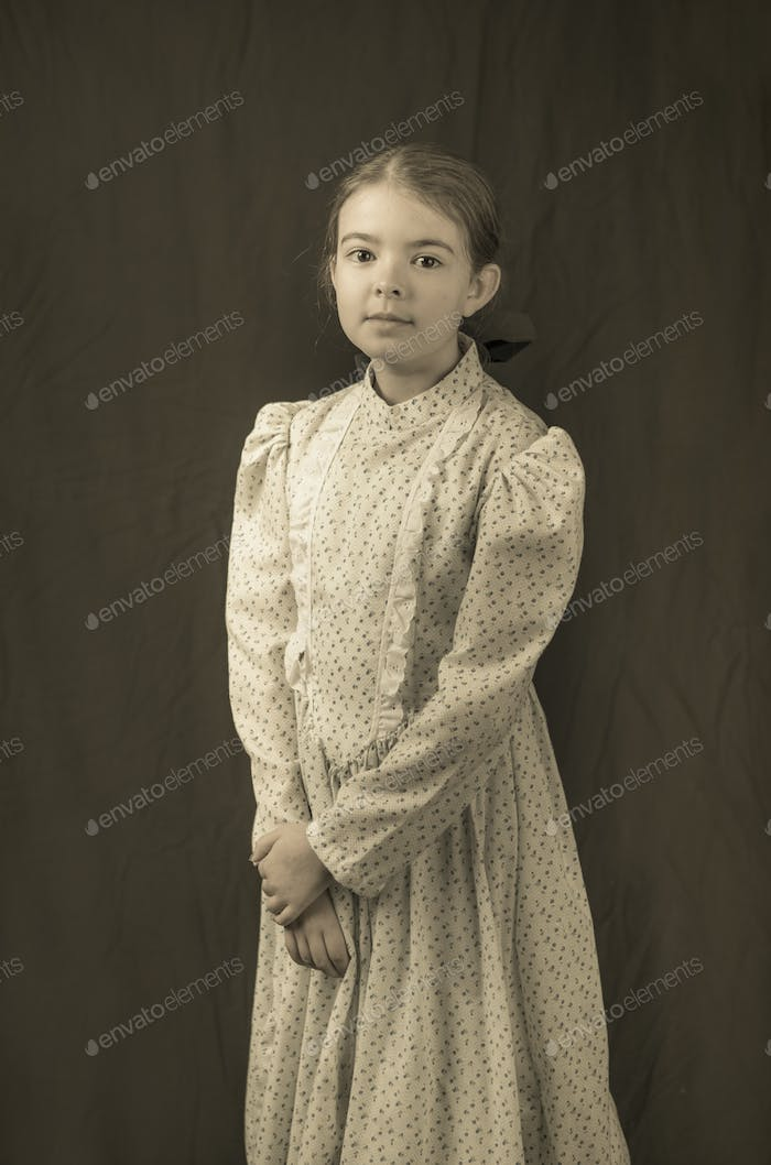 Little girl in early 20th century clothing in replica antique ph