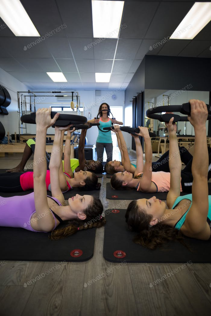 Female trainer assisting group of women with pilates ring exercise