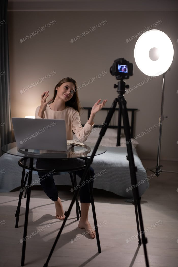Barefoot female recording video for lifestyle vlog