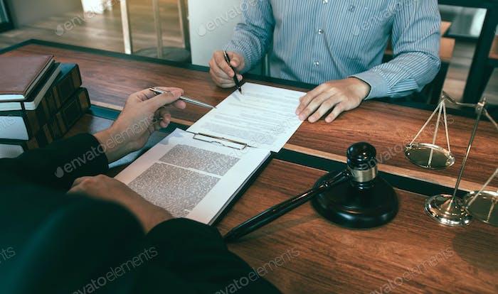 El abogado está explicando al cliente en la oficina sobre las leyes de irregularidades relacionadas con el fraude.