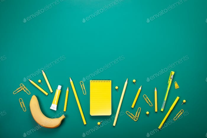 Yellow school supplies over the green board. Education, studing and back to school concept