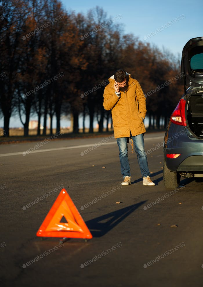 Driver man examining damaged automobile cars