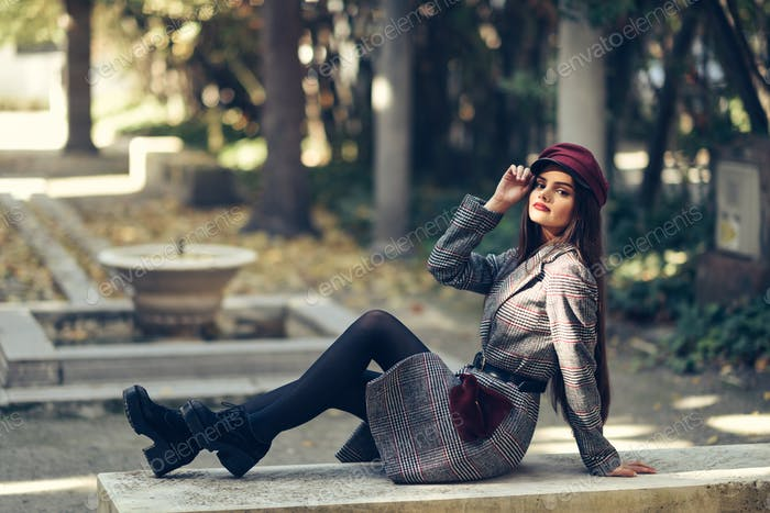 Young beautiful girl wearing winter coat and cap sitting on a bench in urban park