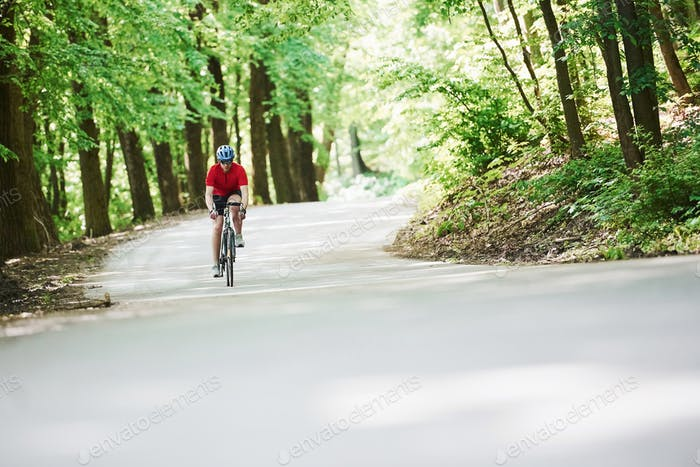 Long way. Cyclist on a bike is on the asphalt road in the forest at sunny day