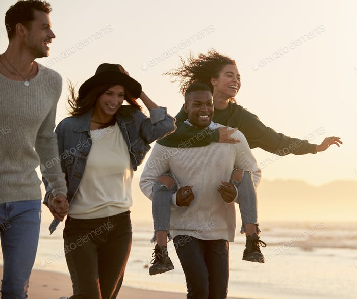 Group Of Friends Having Fun Running Along Winter Beach Together