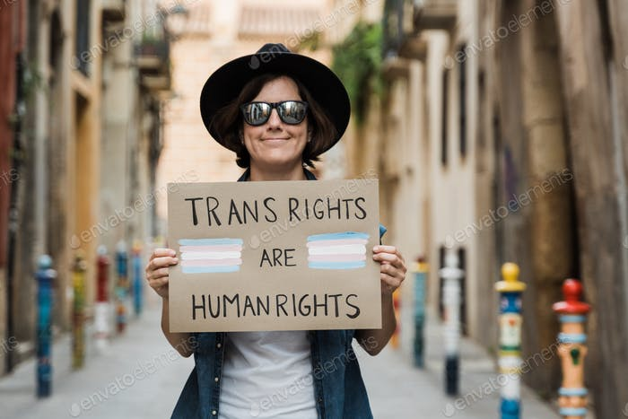 Transgender hipster woman fighting for transsexual human rights at gay pride holding banner