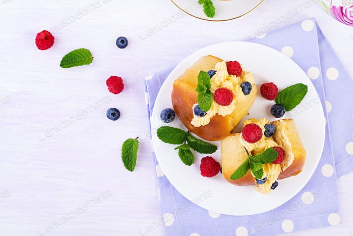 Rum baba decorated with whipped cream and fresh raspberry, blueberry.