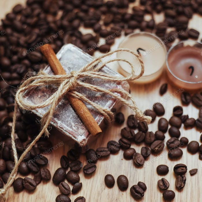 Organic soap with coffee beans and spices, on wooden background.