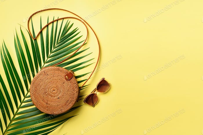 Round rattan bag, sunglasses on yellow background. Banner. Top view with copy space. Trendy bamboo