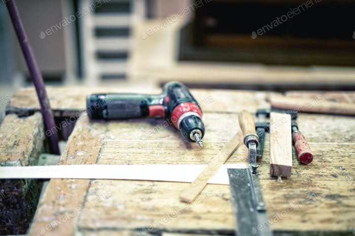 Cordless screwdriver and carpenter tools in wood industrial factory