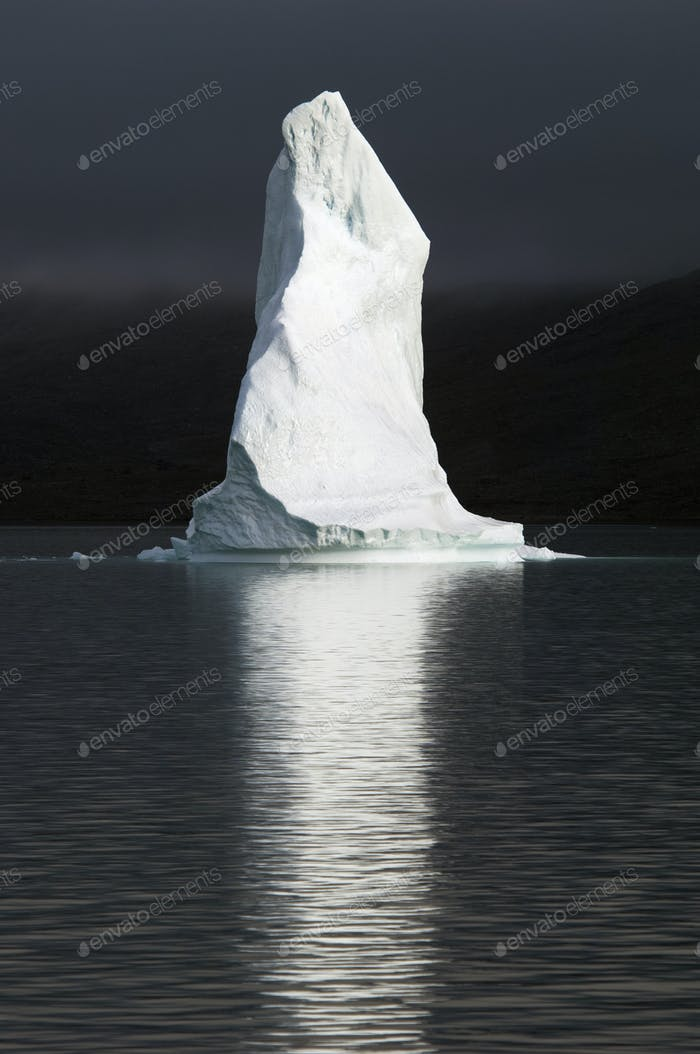 A tall pillar of ice, the top of an iceberg lit up floating on the sea, reflected in the water.