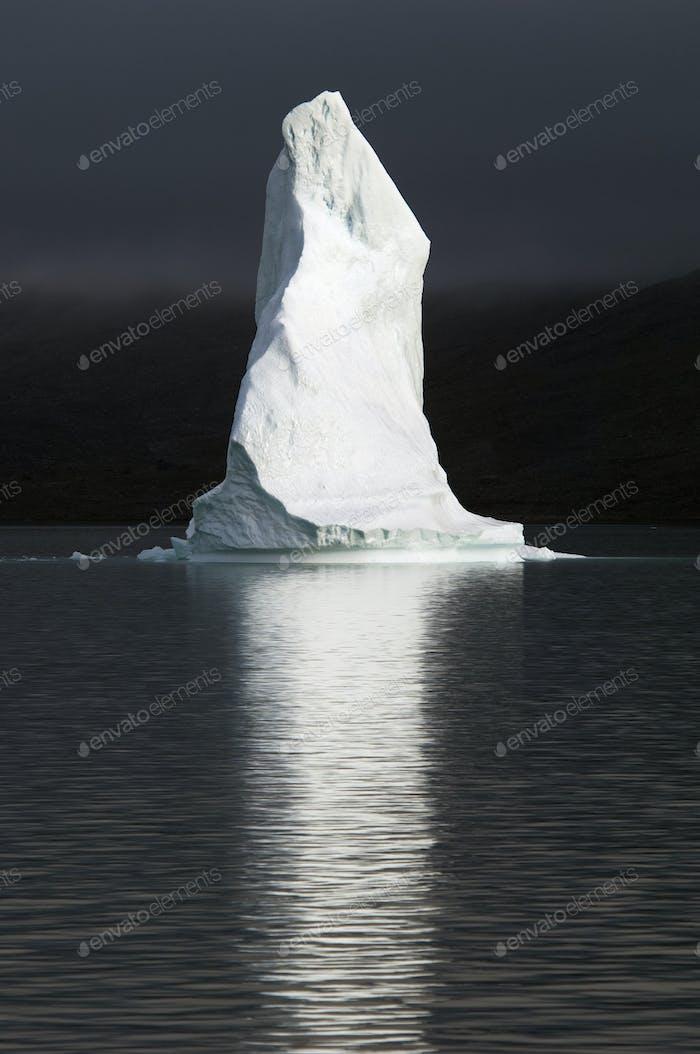 Eine hohe Eissäule, die Spitze eines Eisbergs leuchtete, schwimmend auf dem Meer, reflektiert im Wasser.