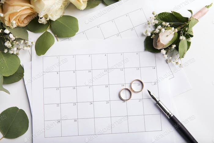 Wedding rings choosing the date in paper calendar