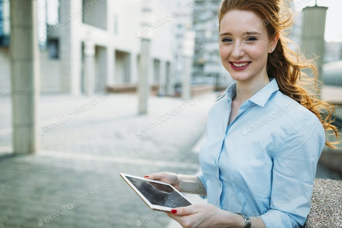 Attractive young businesswoman using digital tablet outside