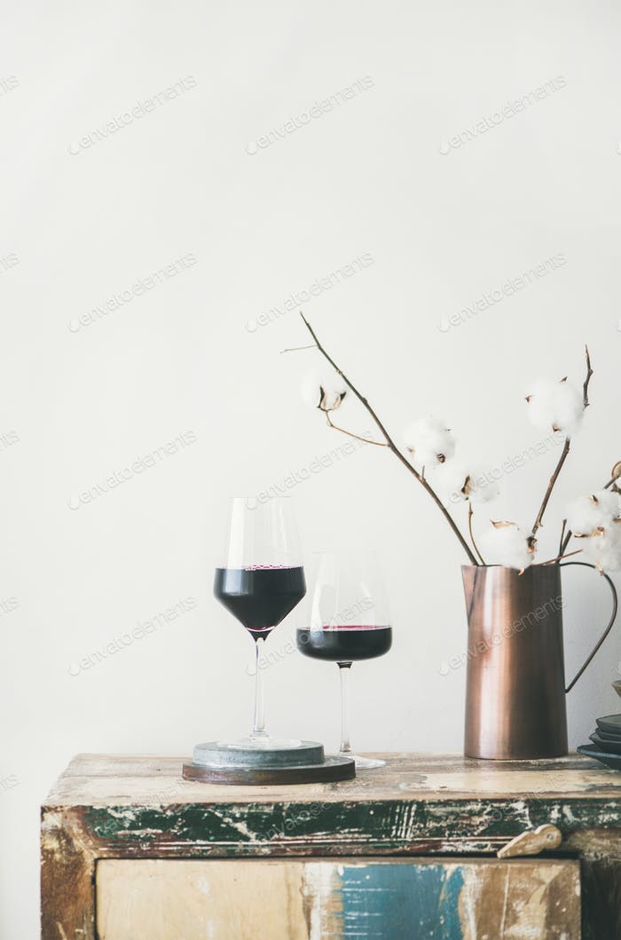 Two glasses of red wine over rustic countertop, copy space