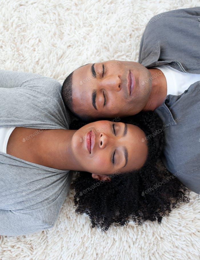 Afro-American couple sleeping on the floor