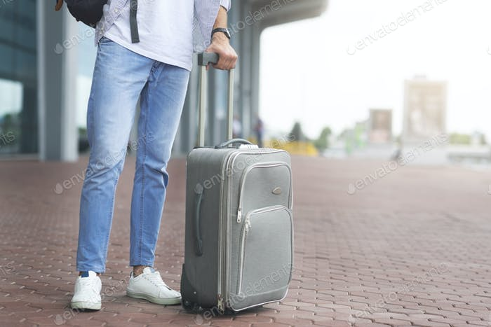 Millennial man standing with luggage at airport exterior