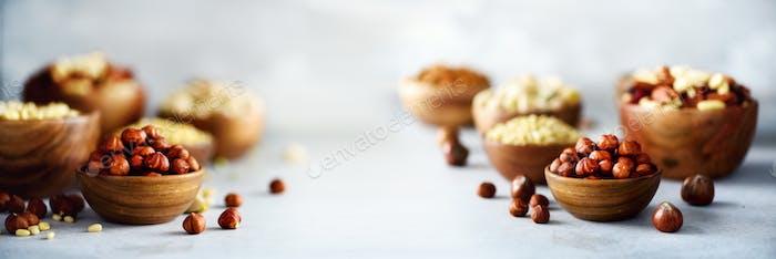Assortment of nuts in wooden bowls. Cashew, hazelnuts, walnuts, pistachio, pecans, pine nuts, peanut