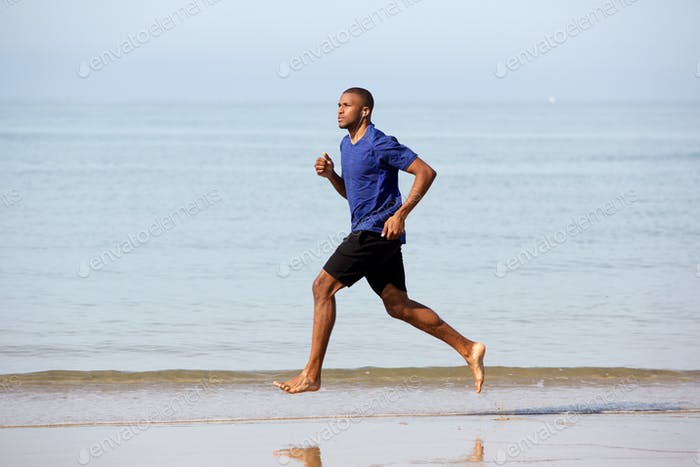 Full body young african male running along sea shore